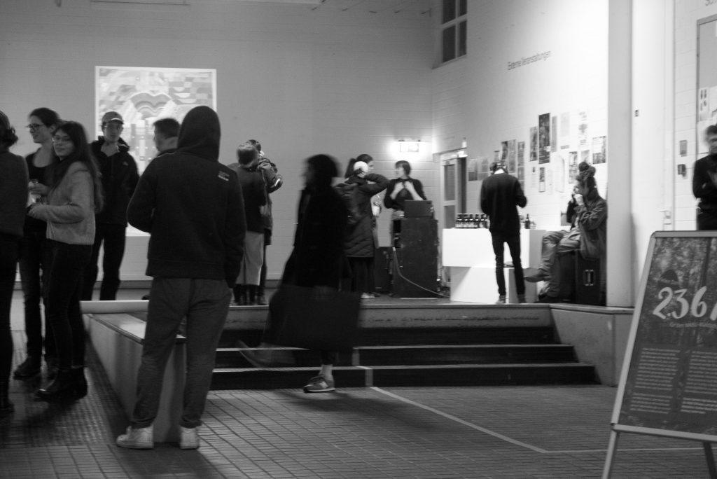 Ausstellungserföffnung im Hochschulfoyer, Menschen stehen herum und unterhalten sich, im Hintergrund steht ein DJ Pult.