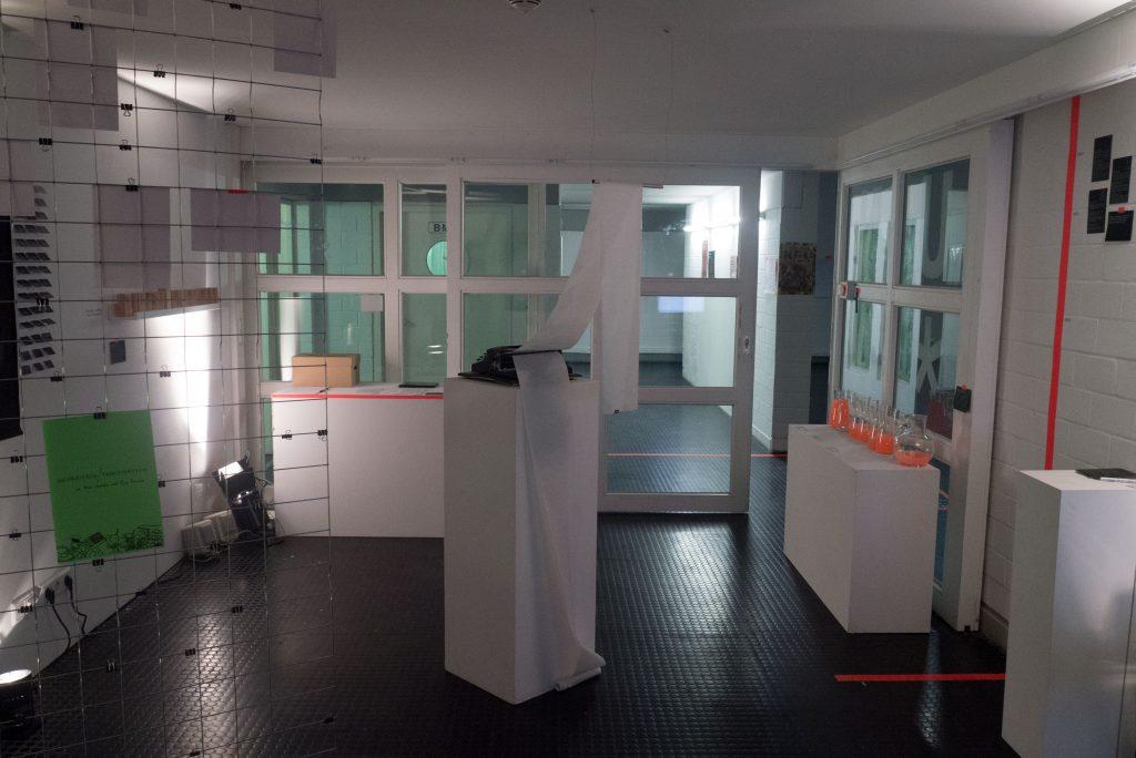 Ausstellungsraum des Zukunfts*archivs: zu sehen sind verschiedene interaktive Ausstellungselemente, so gibt es rechts zum Beispiel eine Abstimmung wo man Fragen beantwortet in dem man eine Flüssigkeit in Antwortgläser gießt. In der Mitte des Raumes steht eine Schreibmaschine für ein gemeinsames Manifest.