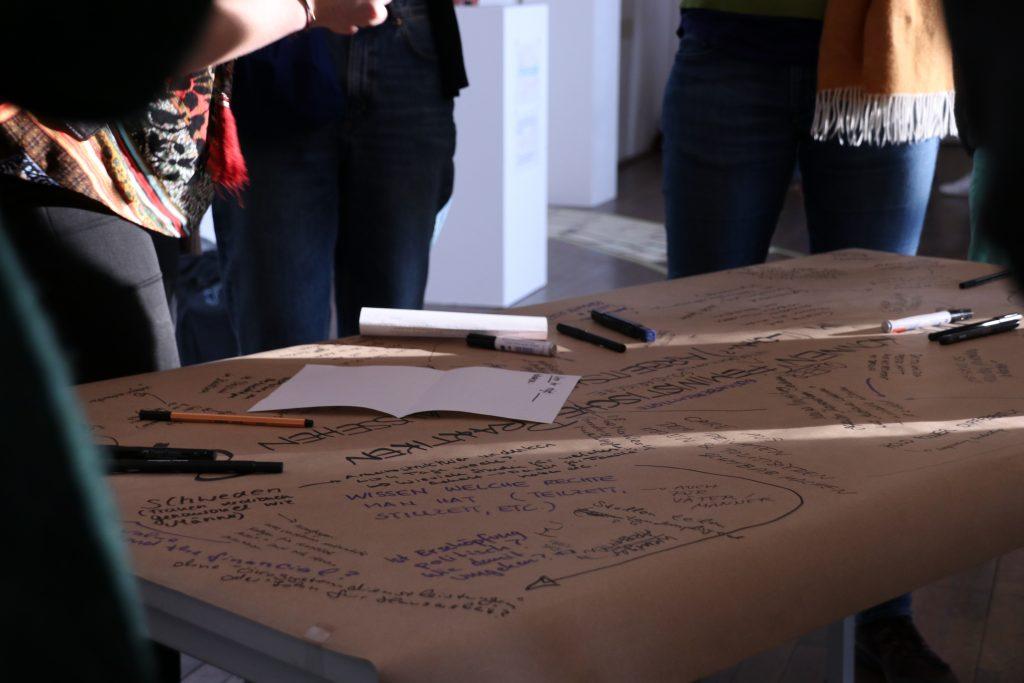 Aufnahme aus einer Workshopsituation: Menschen stehen um einen Tisch herum auf dem eine großes wild beschriftetes Papier liegt.