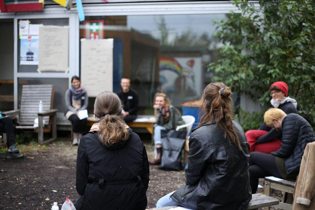 Workshopsituation: Menschen sitzen draußen im Kreis vor einem Gebäude an dessen Fenstern Workshoppapiere hängen.