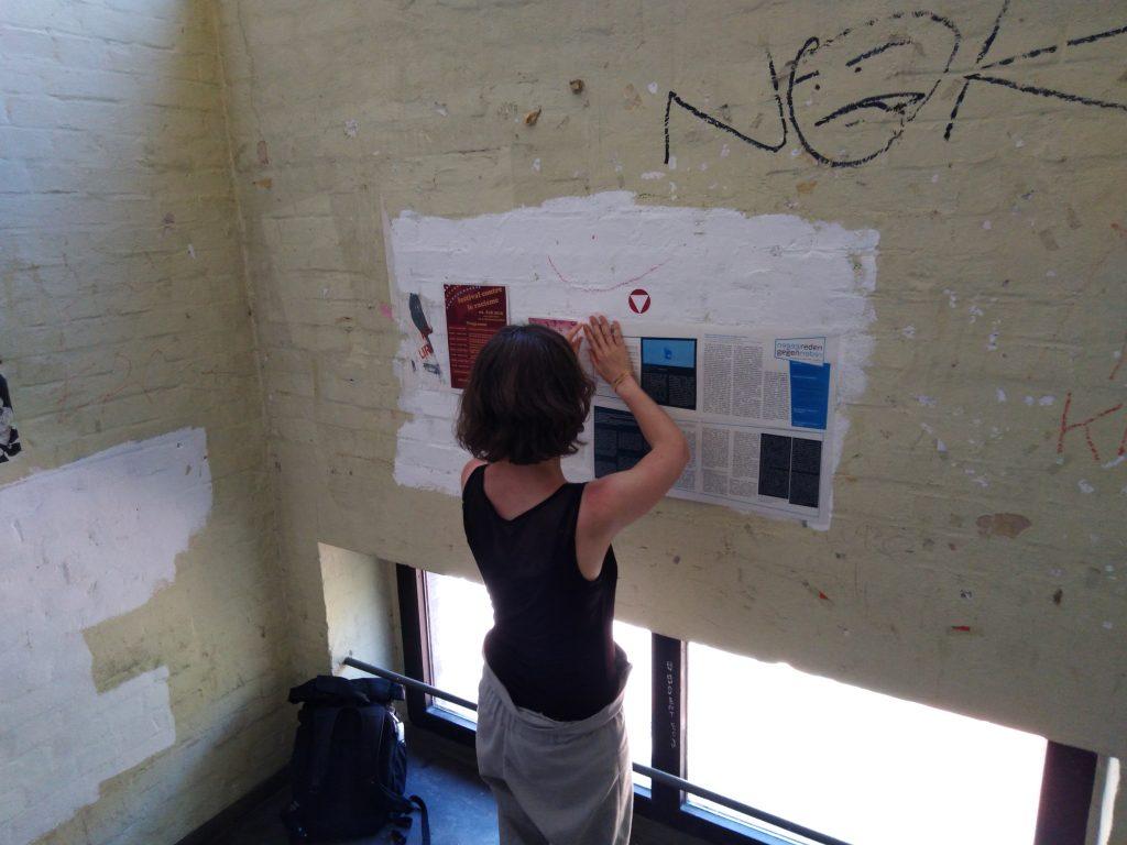 """Die Wandzeitung """"gegenreden"""" wird in einem öffentlichen Gebäude an die Wand gehängt."""