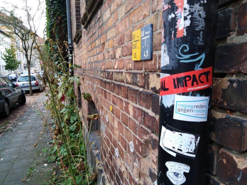 """""""gegenreden"""" Sticker an einer Dachrinne vor einem Haus aus Ziegelsteinen."""